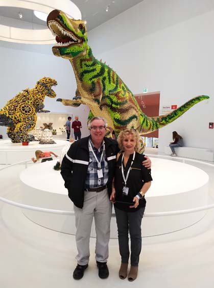 Larry and Eliska in front of the System Dinosaur at LEGO House