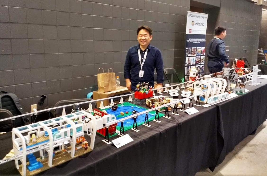 Marvin Park, BrickLink, looks over the AFOL Design Program exhibit.